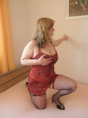 temperamentní kočička v erotických šatech na posteli si drží prsa